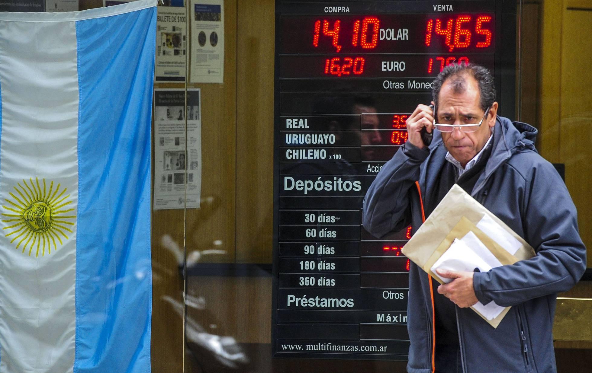 Un argentino pasa por delante de una pizarra con la cotización del dólar en Buenos Aires