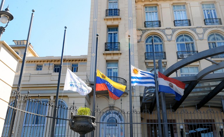"""Flags flutter at half-mast at the Mercosur headquarters in Montevideo, on March 6, 2013, in mourning for the death of Venezuelan President Hugo Chavez on the eve. Condolences poured in Wednesday from world leaders who had found common cause with Venezuela's Hugo Chavez in his 14-year campaign to galvanize the Latin American left and defy US """"imperialism."""" AFP PHOTO/Miguel ROJO"""
