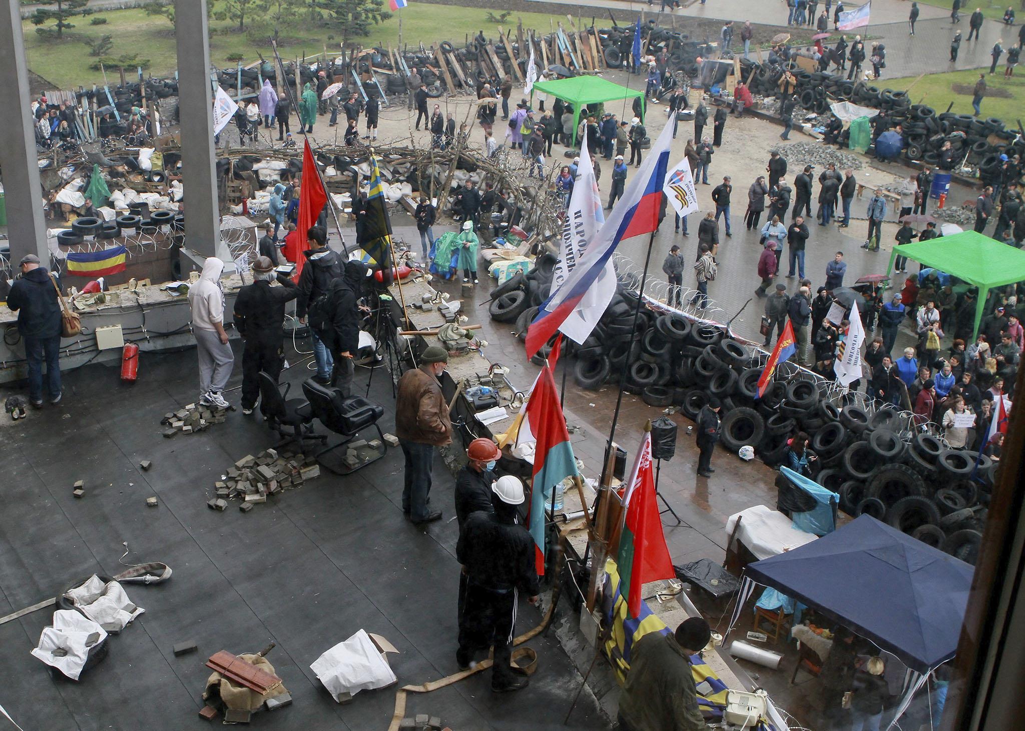 DO04. DONETSK (UCRANIA), 10/04/2014.- Manifestantes prorrusos protestan frente al edificio ocupado de la sede gubernamental de Donetsk, Ucrania, el 10 de abril del 2014. Las regiones de Donetsk y Lugansk, en el sureste industrial de Ucrania, se mantienen firmes en su pulso con las autoridades de Kiev a pesar de las amenazas del Gobierno central, que prometió liberar, incluso por la fuerza, las sedes administrativas ocupadas por los habitantes prorrusos. EFE/Photomig
