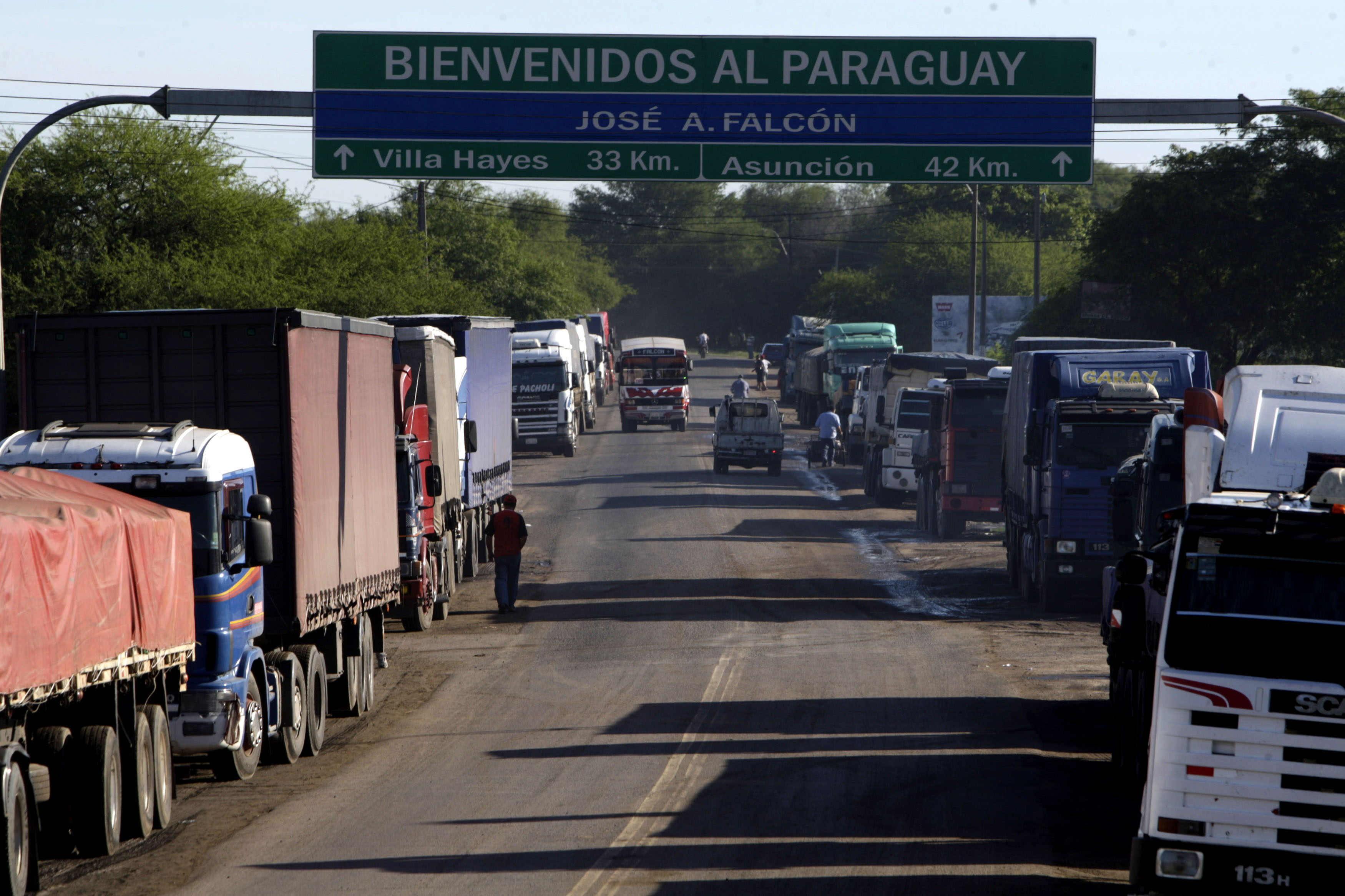 ACOMPAÑA CRÓNICA PARAGUAY ECONOMÍA ASU10. ASUNCIÓN (PARAGUAY), 07/12/2013.- Una fotografía de este 4 de diciembre de 2013 muestra una fila de camiones que se mantiene a un lado de la vía del puente del puerto Falcón que une a Asunción (Paraguay) con Clorinda (Argentina). El Gobierno paraguayo, apremiado por industriales, grandes supermercados y sus propias pérdidas tributarias, intenta poner coto al tradicional contrabando en las fronteras con Argentina y Brasil, que se ha exacerbado con la caída del peso argentino frente al guaraní. Cientos de personas cada día cargan sobre su espalda enormes paquetes de tela con productos al atravesar el control fronterizo que separa la ciudad argentina de Clorinda con la paraguaya Puerto Falcón, cercana a Asunción. EFE/Andrés Cristaldo
