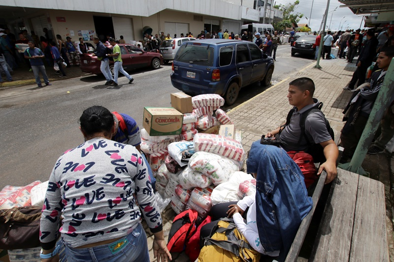 People sit next to bags filled with staple items while they wait for transportation in Pacaraima, Brazil August 3, 2016. Picture taken August 3, 2016. REUTERS/William Urdaneta FOR EDITORIAL USE ONLY. NO RESALES. NO ARCHIVES.