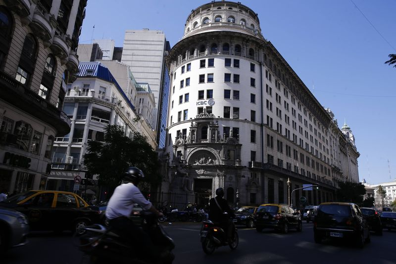 Cars and motorcycles are seen driving by the ICBC building in Buenos Aires' financial district