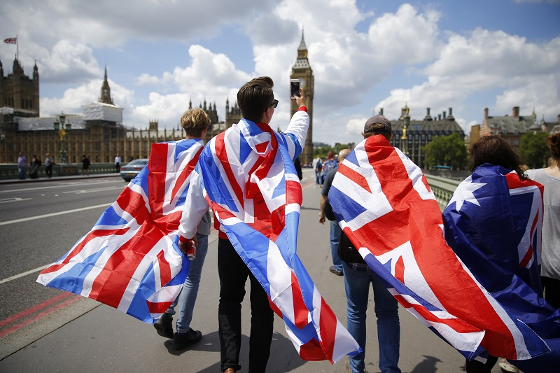 People walk over Westminster Bridge wrapped in Union flags, towards the Queen Elizabeth Tower (Big Ben) and The Houses of Parliament in central London on June 26, 2016. Britain's opposition Labour party plunged into turmoil Sunday and the prospect of Scottish independence drew closer, ahead of a showdown with EU leaders over the country's seismic vote to leave the bloc. Two days after Prime Minister David Cameron resigned over his failure to keep Britain in the European Union, Labour leader Jeremy Corbyn faced a revolt by his lawmakers who called for him, too, to quit. / AFP PHOTO / Odd ANDERSEN