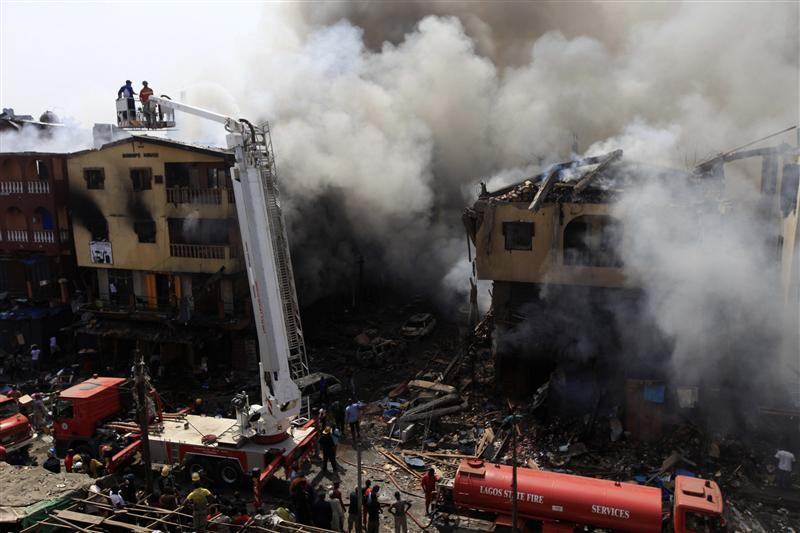 Firefighters use a crane to try extinguish a fire after fireworks stored in a building exploded in a densely populated area in the Isale Eko district in Nigeria's commercial capital of Lagos December 26, 2012. REUTERS/Akintunde Akinleye (NIGERIA - Tags: DISASTER TPX IMAGES OF THE DAY)
