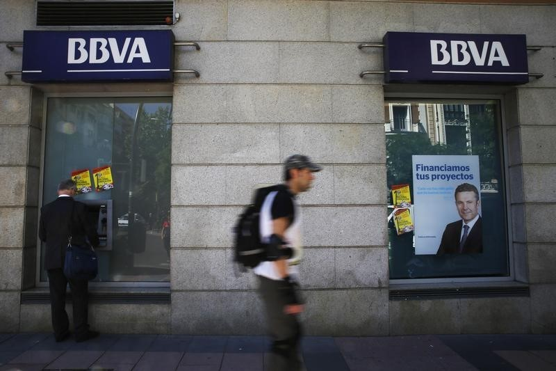 A man (L) uses an ATM machine at a BBVA bank branch in Madrid April 30, 2014. REUTERS/Susana Vera