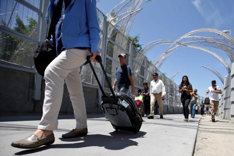 En esta imagen, tomada el 18 de agosto de 2015, peatones cargan con maletas y otros bienes por el nuevo paso fronterizo de México en San Ysidro, California. (Foto AP/Lenny Ignelzi)