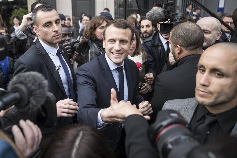 El candidato socioliberal a la presidencia francesa, Emmanuel Macron (c), saluda tras visitar una comisaría de policía durante un acto de campaña electoral en París, Francia, hoy, 13 de marzo de 2017. EFE