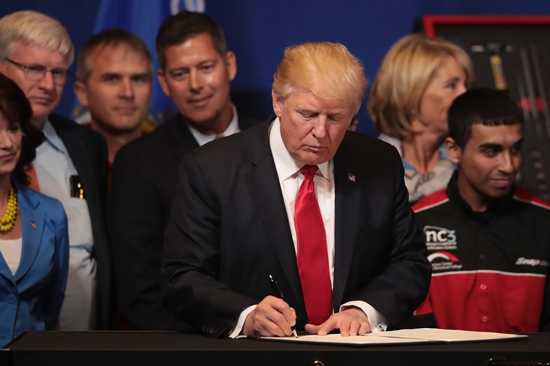 KENOSHA, WI - APRIL 18: President Donald Trump signs an executive order to try to bring jobs back to American workers and revamp the H-1B visa guest worker program during a visit to the headquarters of tool manufacturer Snap-On on April 18, 2017 in Kenosha, Wisconsin.   Scott Olson/Getty Images/AFP
