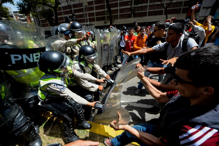 Opposition activists scuffle with riot police during a protest against President Nicolas Maduro's government in Caracas on April 4, 2017.  Activists clashed with police in Venezuela Tuesday as the opposition mobilized against moves to tighten President Nicolas Maduro's grip on power. Protesters hurled stones at riot police who fired tear gas as they blocked the demonstrators from advancing through central Caracas, where pro-government activists were also planning to march. / AFP PHOTO / FEDERICO PARRA