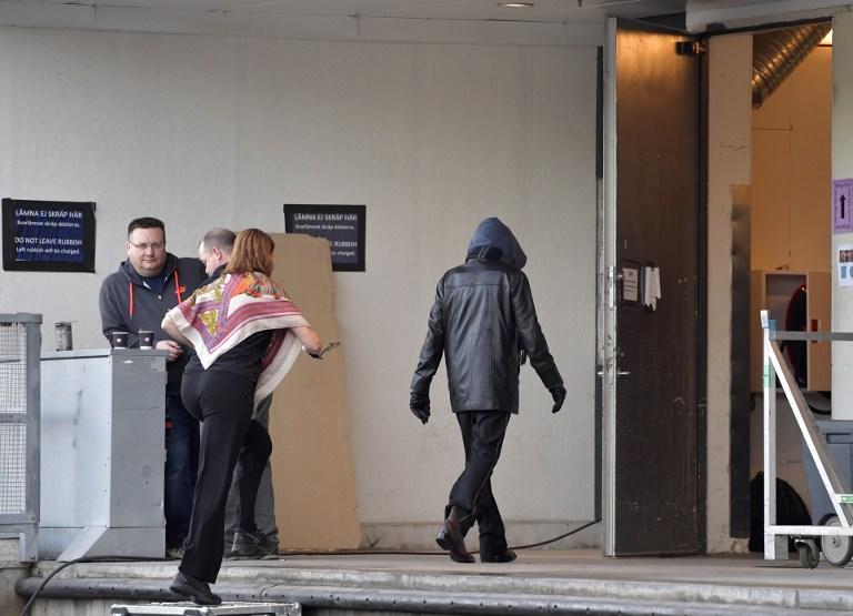 Una persona que supuestamente es el artista estadounidense Bob Dylan llevando una chaqueta negra y una sudadera con capucha es fotografiada mientras entra en la puerta del backstage en Stockholm Waterfront el 1 de abril de 2017, donde Bob Dylan está realizando la misma noche. AFP