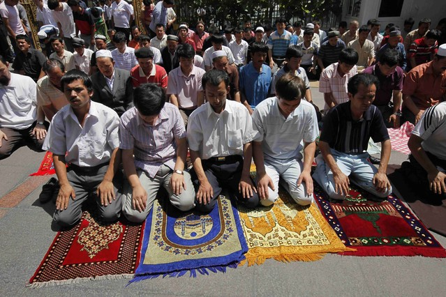 Uighur men pray on their own in a mosque despite city wide closure of the mosques in Urumqi, western China's Xinjiang province, Friday, July 10, 2009.  Several mosques in riot-hit Urumqi opened for Friday prayers after boisterous crowds gathered outside, despite notices posted earlier saying they would be closed in the wake of ethnic violence that left 156 dead. (AP Photo/Eugene Hoshiko)