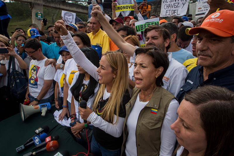 Opositores venezolanos reclaman libertad de presos políticos frente a cárceles