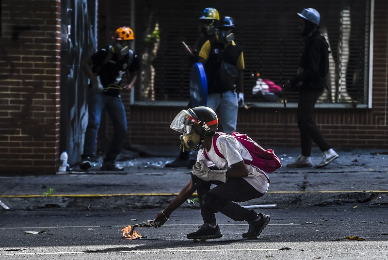 Opposition demonstrators clash with riot police in Caracas, on May 24, 2017. Venezuela's President Nicolas Maduro formally launched moves to rewrite the constitution on Tuesday, defying opponents who accuse him of clinging to power in a political crisis that has prompted deadly unrest. / AFP PHOTO / JUAN BARRETO