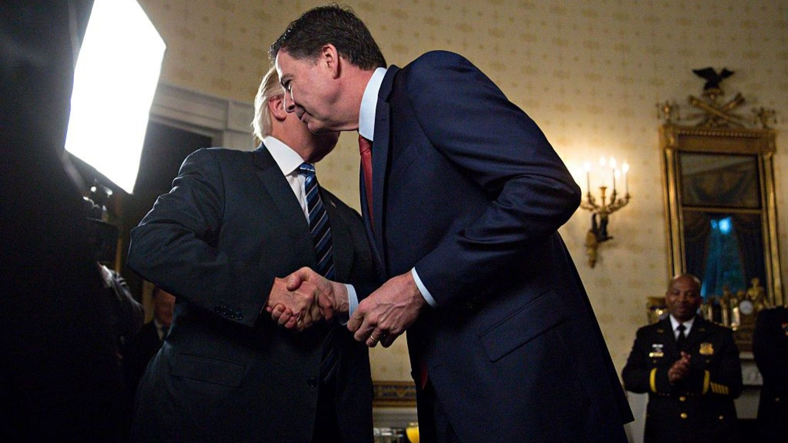 """WASHINGTON, DC - JANUARY 22: U.S. President Donald Trump (L) shakes hands with James Comey, director of the Federal Bureau of Investigation (FBI), during an Inaugural Law Enforcement Officers and First Responders Reception in the Blue Room of the White House on January 22, 2017 in Washington, DC. Trump today mocked protesters who gathered for large demonstrations across the U.S. and the world on Saturday to signal discontent with his leadership, but later offered a more conciliatory tone, saying he recognized such marches as a """"hallmark of our democracy."""" (Photo by Andrew Harrer-Pool/Getty Images)"""