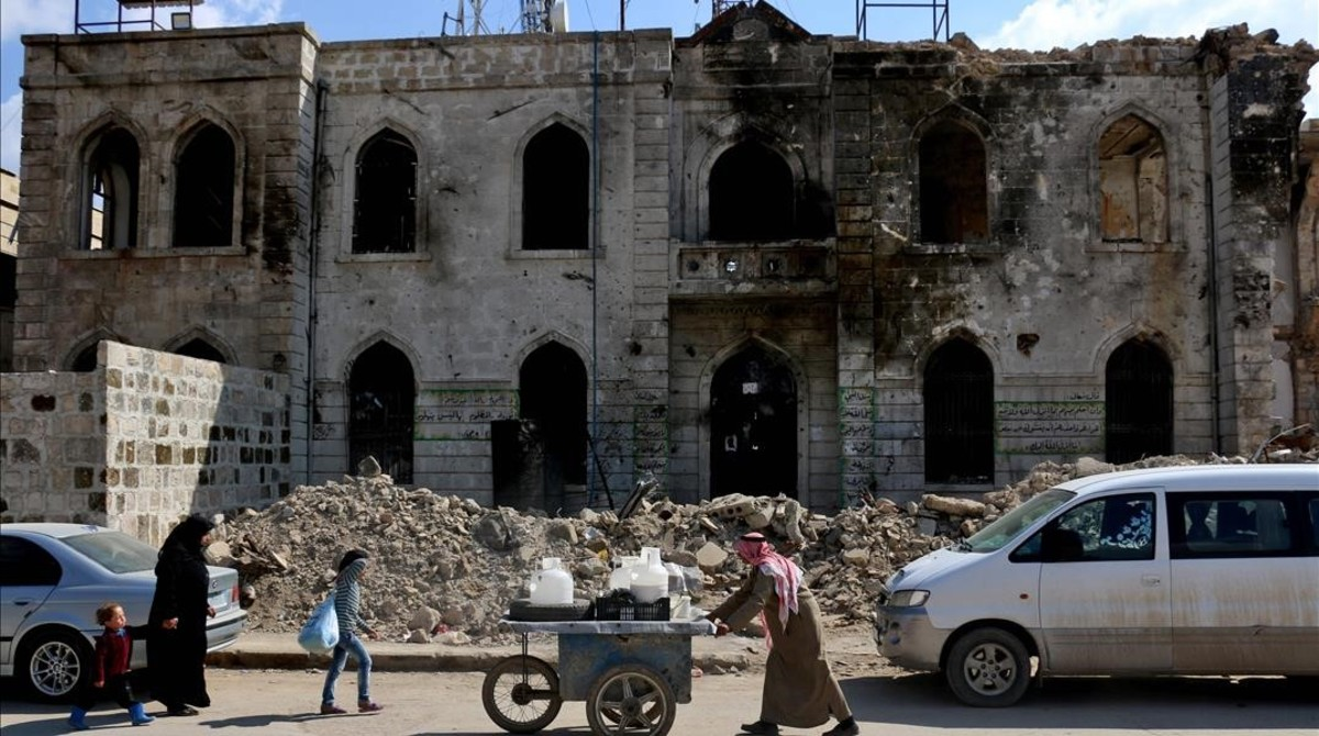 TOPSHOT - A street peddler man pushes a cart carrying plastic liquid containers down a street past the damaged courthouse building in the city of Azaz  on Syria s northern border with Turkey  on April 17  2017    AFP PHOTO   Zein Al RIFAI
