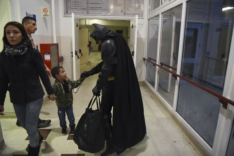 Argentine Batman, greets a boy in a corridor of the 'Sor Maria Ludovica' children's Hospital in La Plata, 60 kilometres south of Buenos Aires, on June 2, 2017. The Argentine Batman has made La Plata children's hospital a target of laughter and treats against pain. / AFP PHOTO / Eitan ABRAMOVICH
