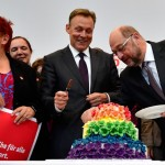 Thomas Oppermann (C), parliamentary group leader of the social democratic SPD party, and SPD leader and candidate for chancellor Martin Schulz (R) cut a wedding cake in rainbow colors and decorated with figurines of two women and two men at the Bundestag (lower house of parliament) in Berlin on June 30, 2017. The German parliament legalised same-sex marriage, days after Chancellor Angela Merkel said she would allow her conservative lawmakers to follow their conscience in the vote. / AFP PHOTO / Tobias SCHWARZ