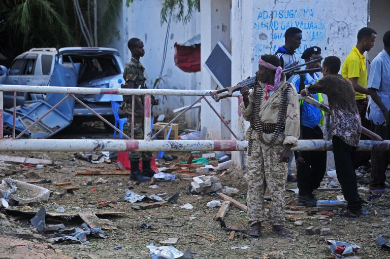Somali security forces patrol at the site of a terror attack outside the Pizza House restaurant in Mogadishu on June 15, 2017. A suicide car bombing and assault by Shabaab militants on two neighbouring restaurants in Somalia's capital Mogadishu ended Thursday morning with 18 dead, a government spokesman said. The attack began at around 8pm (17.00GMT) on the evening of June 14 with a suicide car bombing at the Post Treats restaurant and club, after which gunmen stormed inside the nearby Pizza House restaurant. / AFP PHOTO / Mohamed ABDIWAHAB