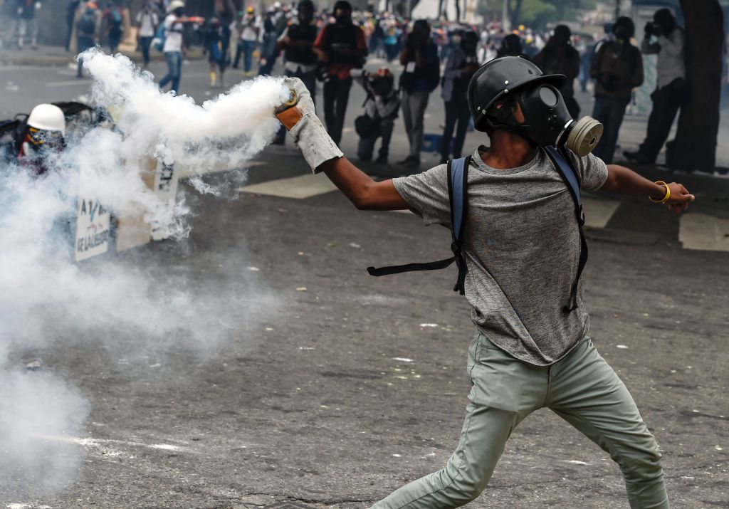 "A demonstrator hurls back a tear gas canister at riot police during a protest against President Nicolas Maduro, in Caracas on May 8, 2017. Venezuela's opposition mobilized Monday in fresh street protests against President Nicolas Maduro's efforts to reform the constitution in a deadly political crisis. Supporters of the opposition Democratic Unity Roundtable (MUD) gathered in eastern Caracas to march to the education ministry under the slogan ""No to the dictatorship.""  / AFP / JUAN BARRETO"