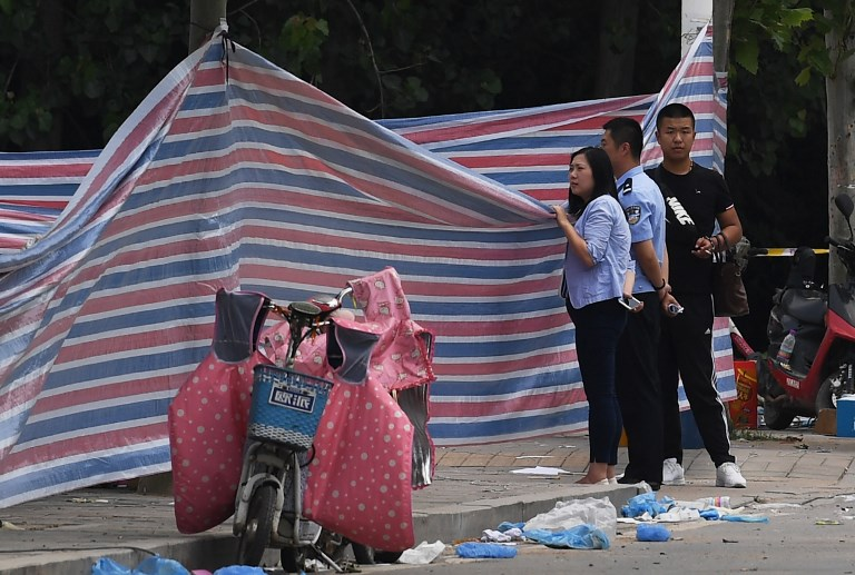 Police officers peer over a screen placed outside a kindergarten where an explosion killed 8 people and injured dozens a day earlier, in Fengxian, in China's eastern Jiangsu province on June 16, 2017. Police investigating the explosion say they are treating the incident as a crime and have identified at least one suspect. / AFP PHOTO / GREG BAKER