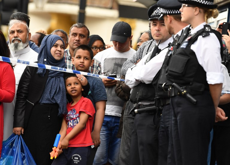 "A boy holds a toy gun as police officers stand on duty inside a cordon in East Ham in east London on June 4, 2017, following a raid on a property as police continue their investigations following the June 3 terror attacks in central London. British Prime Minister Theresa May blamed ""evil"" Islamist ideology Sunday for an attack by knife-wielding men who mowed down and stabbed revellers in London, killing seven, as police said they had arrested 12 suspects. / AFP PHOTO / Justin TALLIS"