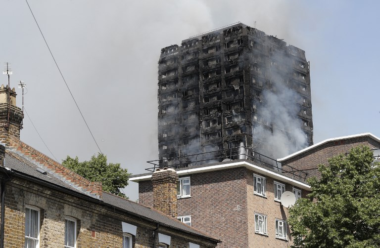 Smoke billows from Grenfell Tower, a residential block of flats on June 14, 2017 in west London, as firefighters continue to control a fire.  Shaken survivors of a blaze that ravaged a west London tower block told Wednesday of seeing people trapped or jump to their doom as flames raced towards the building's upper floors and smoke filled the corridors.   / AFP PHOTO / Adrian DENNIS