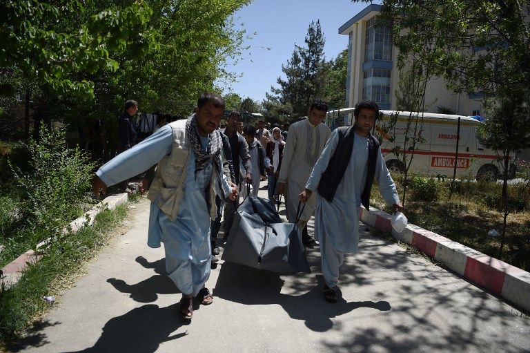 (FILES) This file photo taken on May 31, 2017 shows Afghan volunteers carrying the body of a resident killed in a car bomb attack to the Wazir Akbar Khan hospital in Kabul. Civilian deaths in Afghanistan hit a record high in the first half of 2017, with 1,663 killed and more than 3,500 injured, the United Nations said July 17.  / AFP PHOTO / WAKIL KOHSAR