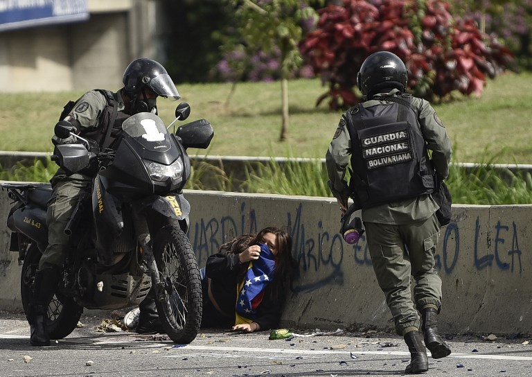 Members of the National Guard arrest an opposition activist during a protest against Venezuelan President Nicolas Maduro in Caracas on July 10, 2017.  Venezuela hit its 100th day of anti-government protests Sunday, amid uncertainty over whether the release from prison a day earlier of prominent political prisoner Leopoldo Lopez might open the way to negotiations to defuse the profound crisis gripping the country. / AFP PHOTO / CARLOS BECERRA