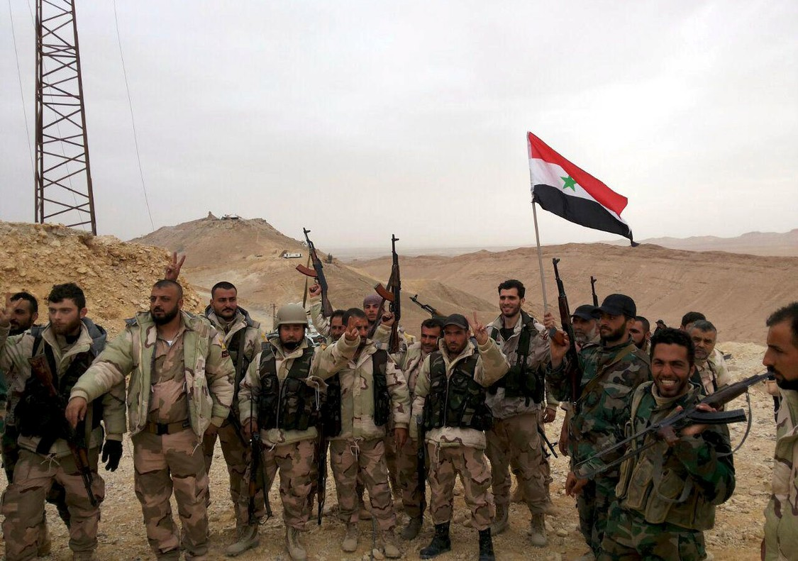 Forces loyal to Syria's President Bashar al-Assad flash victory signs and carry a Syrian national flag on the edge of the historic city of Palmyra in Homs Governorate, in this file handout picture provided by SANA on March 26, 2016. Syrian government forces recaptured Palmyra on March 27, state media and a monitoring group said, inflicting a significant defeat on the Islamic State group which had controlled the desert city since May last year. REUTERS/SANA/Handout via Reuters/Files ATTENTION EDITORS - THIS PICTURE WAS PROVIDED BY A THIRD PARTY. REUTERS IS UNABLE TO INDEPENDENTLY VERIFY THE AUTHENTICITY, CONTENT, LOCATION OR DATE OF THIS IMAGE. FOR EDITORIAL USE ONLY. NOT FOR SALE FOR MARKETING OR ADVERTISING CAMPAIGNS. THIS PICTURE IS DISTRIBUTED EXACTLY AS RECEIVED BY REUTERS, AS A SERVICE TO CLIENTS