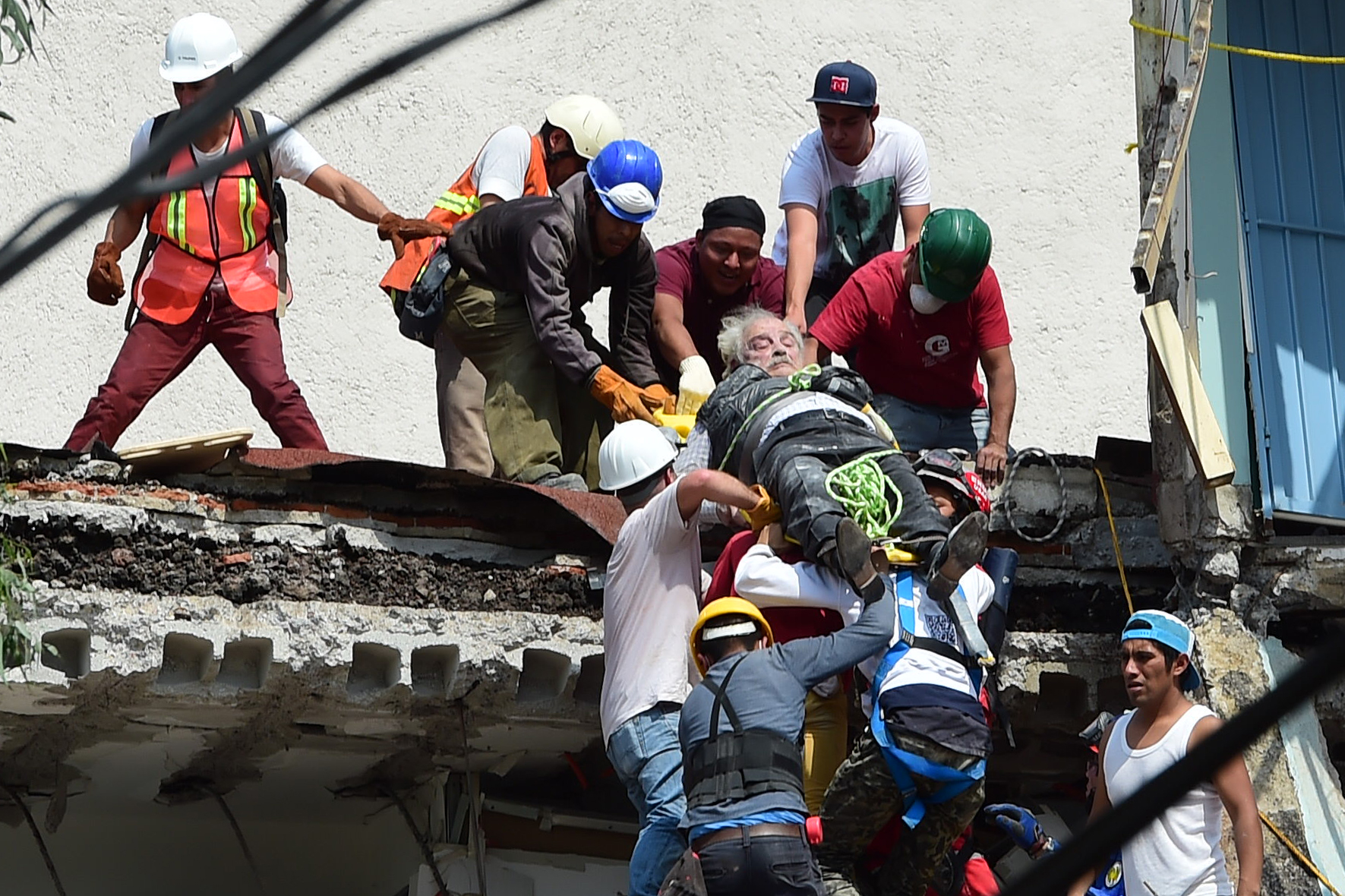 A man is pulled out of the rubble alive following a quake in Mexico City on September 19, 2017. A powerful earthquake shook Mexico City on Tuesday, causing panic among the megalopolis' 20 million inhabitants on the 32nd anniversary of a devastating 1985 quake. The US Geological Survey put the quake's magnitude at 7.1 while Mexico's Seismological Institute said it measured 6.8 on its scale. The institute said the quake's epicenter was seven kilometers west of Chiautla de Tapia, in the neighboring state of Puebla.  / AFP PHOTO / Ronaldo SCHEMIDT