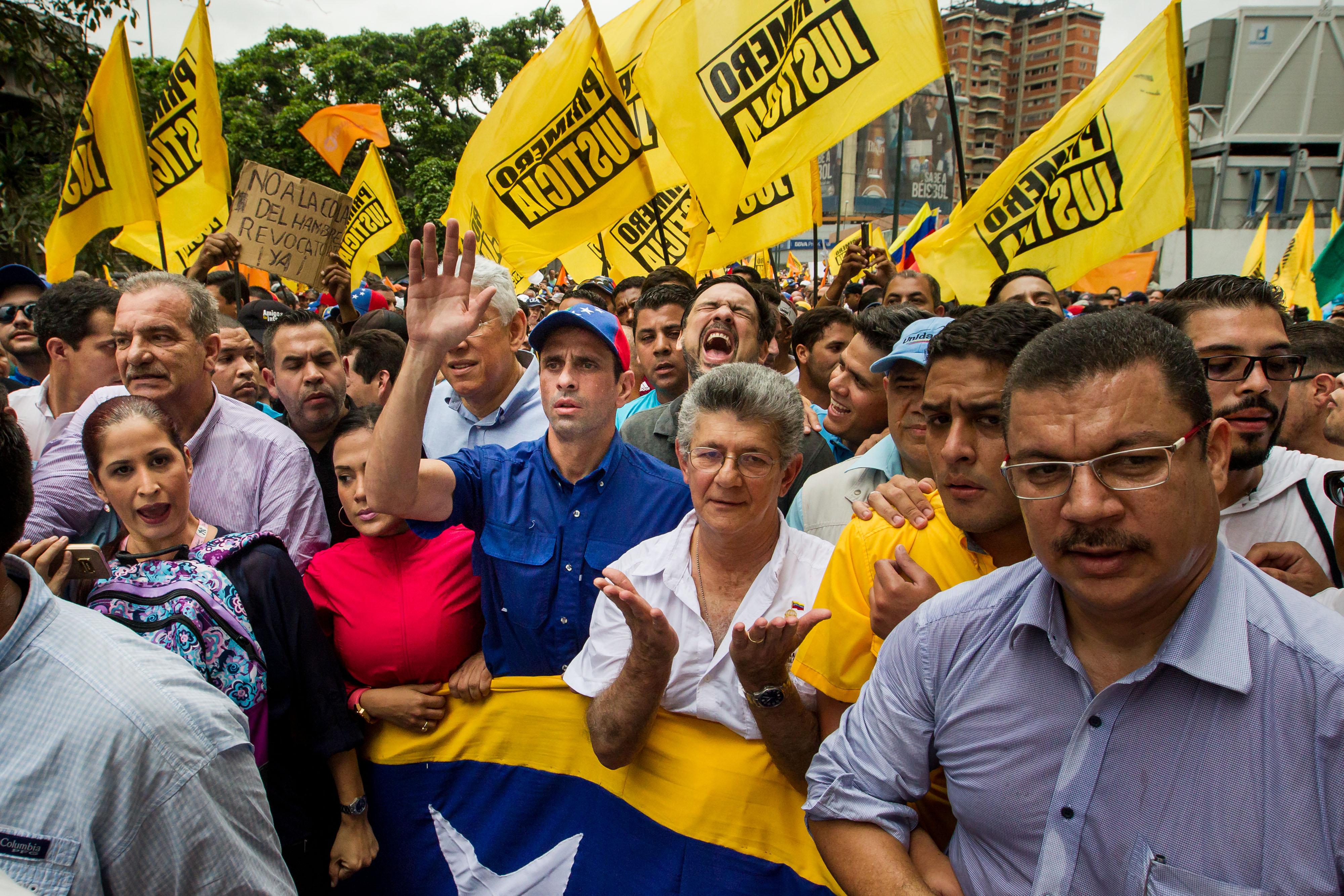 CAR05. CARACAS (VENEZUELA), 11/05/2016.- El líder opositor Henrique Capriles (c-i) y el presidente de la Asamblea Nacional de Venezuela, Henry Ramos Allup (c-d), participan en una manifestación hoy, miércoles 11 de mayo de 2016, en Caracas (Venezuela). La policía militarizada de Venezuela y la estatal Policía Nacional Bolivariana (PNB) impidieron el paso de la marcha a la que convocó hoy la oposición del país hasta la sede del Poder Electoral para pedir celeridad en la activación de un referendo para revocar al presidente, Nicolás Maduro. EFE/Miguel Gutiérrez
