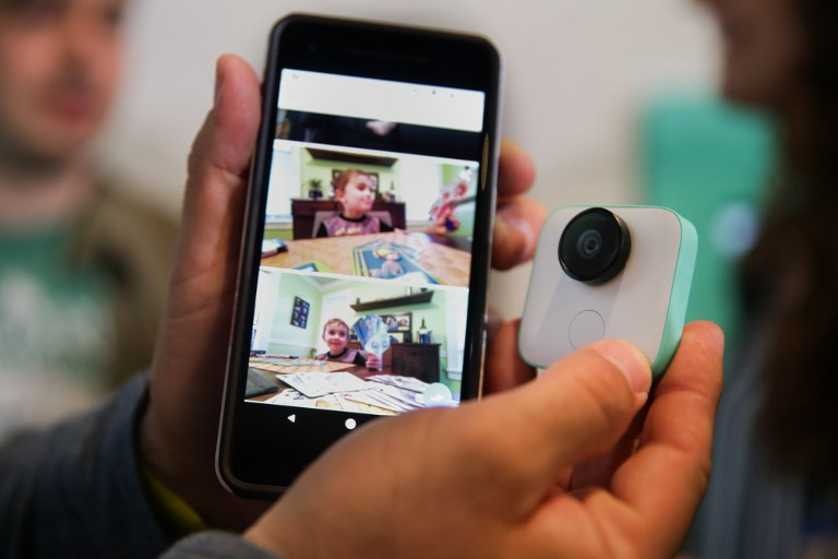 A Google employee holds up the new Pixel 2 smartphone and Google Clips wireless camera at a product launch event on October 4, 2017 at the SFJAZZ Center in San Francisco, California. Google unveiled newly designed versions of its Pixel smartphone, the highlight of a refreshed line of devices which are part of the tech giant's efforts to boost its presence against hardware rivals. / AFP PHOTO / Elijah Nouvelage