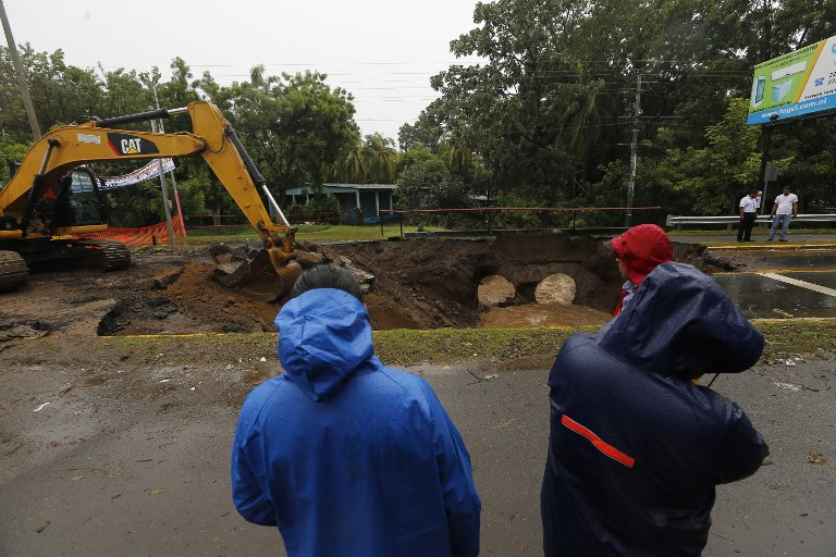 Municipal employees work on damages in the Panamerican Road, following the passage of Tropical Storm Nate, in Rivas, Nicaragua, on October 6, 2017. Tropical Storm Nate gained strength as it headed toward popular Mexican beach resorts and ultimately the US Gulf coast after dumping heavy rains in Central America that left at least 22 people dead. / AFP PHOTO / INTI OCON