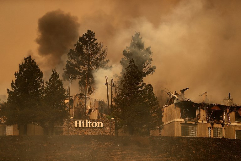 SANTA ROSA, CA - OCTOBER 09: Smoke continues to rise from the Hilton Sonoma Wine Country on October 9, 2017 in Santa Rosa, California. Ten people have died in wildfires that have burned tens of thousands of acres and destroyed over 1,500 homes and businesses in several Northen California counties.   Justin Sullivan/Getty Images/AFP