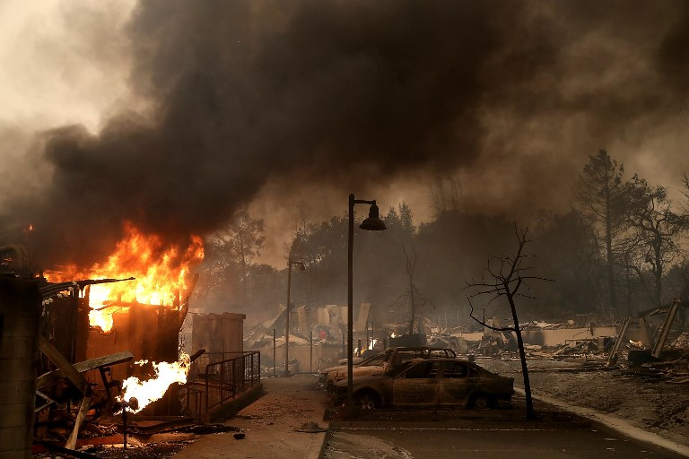 SANTA ROSA, CA - OCTOBER 09: Burned out cars sit next to a building on fire in a fire ravaged neighborhood on October 9, 2017 in Santa Rosa, California. Ten people have died in wildfires that have burned tens of thousands of acres and destroyed over 1,500 homes and businesses in several Northen California counties.   Justin Sullivan/Getty Images/AFP