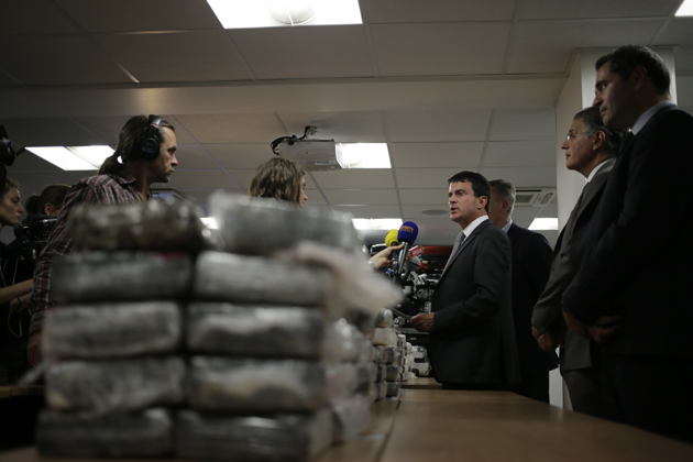 French Interior minister Manuel Valls (C) gives a press conference in front of cocaine seized by French police, on September 21, 2013 in Nanterre, France. Valls announced 1.3 tonnes of pure cocaine was found on board an Air France cargo plane. A source close to the investigation said the flight had originated in the Venezuelan capital Caracas, adding that the haul had a street value of some 200 million euros ($270 million).   AFP PHOTO / KENZO TRIBOUILLARD