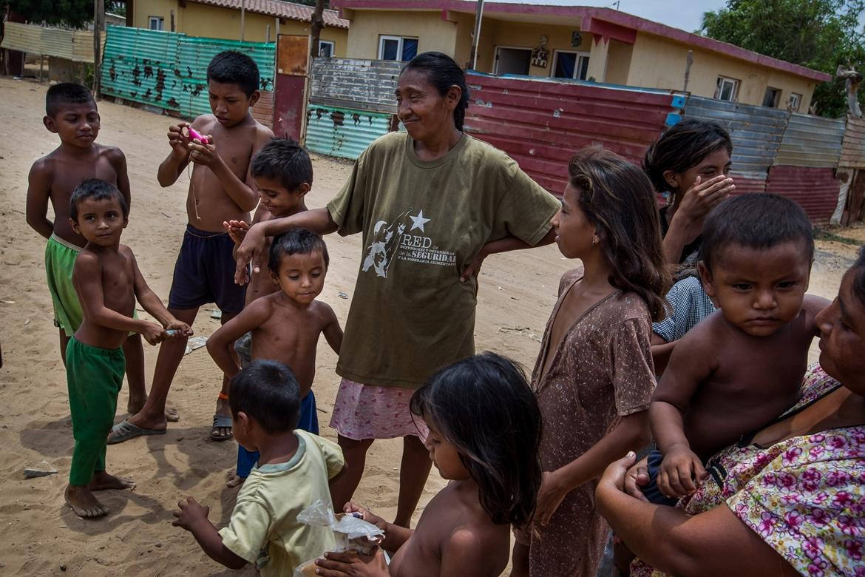 CAR00. MARACAIBO (VENEZUELA), 18/09/2015.- Fotografía del 11 de septiembre del 2015 donde se observa una mujer wayúu con sus hijos en una calle de la localidad de Canchancha en la ciudad de Maracaibo (Venezuela). Sobre la sabana desértica de La Guajira venezolana se levantan las aspas de un parque eólico oxidado y abandonado donde no cae la lluvia, no retoñan las plantas, no engordan los animales, no crecen los niños, pero si los contrabandistas, muchos menores de edad. Tras más de dos años de sequía, los campos guajiros quedaron abandonados y los que una vez fueron árboles hoy son grandes extensiones de ramales secos y repletos de basura en los que las cabras y burros flacos también están olvidados. Ahora el cierre fronterizo del noroccidental estado del Zulia ha encendido un foco sobre la comunidad indígena que habita en el territorio, un asentamiento de 400.000 personas, la mayoría de la etnia wayúu, que vive sin agua y electricidad, signados por la pobreza, el desempleo y la desnutrición. Sobre la sabana desértica de La Guajira se levantan las aspas de un parque eólico oxidado y abandonado donde no cae la lluvia, no retoñan las plantas, no engordan los animales, no crecen los niños y no pasa nada si no es por contrabando. Tras más de dos años de sequía en La Guajira, los campos quedaron abandonados y los que una vez fueron árboles son hoy grandes extensiones llenas de ramales secos repletos de basura en los que las cabras y burros flacos también fueron olvidados. EFE/MIGUEL GUTIERREZ