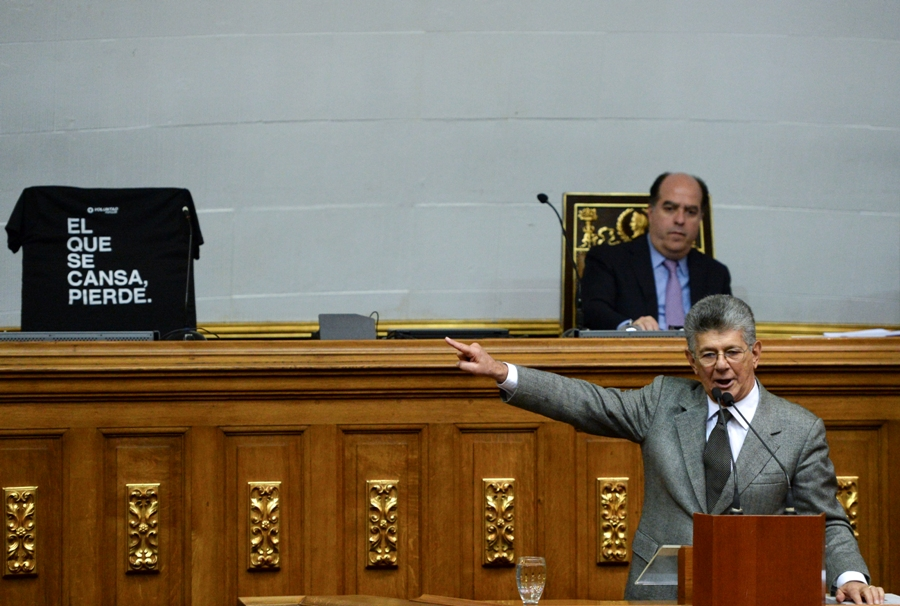 """Opposition deputy Henry Ramos Allup (R) delivers a speech while the President of the Venezuelan opposition-controlled parliament Julio Borges (top) listens to him next to the chair of the vice-president of Venezuela's National Assembly, Freddy Guevara, covered with a shirt that reads """"the one that gets tired loses"""" during a session of the Venezuelan National Assembly in Caracas on November 7, 2017. Guevara on Saturday requested Chile's protection after Venezuela's high court announced he would be prosecuted on charges punishable by a decade in prison. / AFP PHOTO / FEDERICO PARRA"""