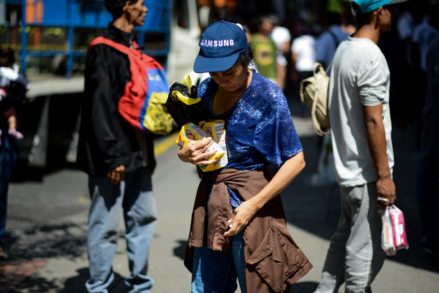 A woman holds two bags of flour after queuing outside a supermarket in Caracas to buy basic foodstuffs and household products on November 10, 2017. In crisis-stricken Venezuela, the cost of the basic basket of goods soared to nearly 2.7 million bolivars in September, the equivalent of six minimum monthly wages. / AFP PHOTO / FEDERICO PARRA