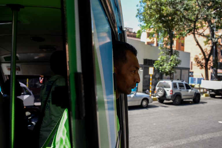 A volunteer looks out of the PanaBus (FriendlyBus) looking for homeless people to assist in Caracas on November 27, 2017. Monday through Friday, the PanaBus (FriendlyBus) makes its way around the Venezuelan capital offering homeless people a shower, clean clothes, a meal, a health check-up and advice to help them out of their plight - a beacon of hope and solidarity in the midst of economic and political crisis and severe shortages of food and medicines. / AFP PHOTO / FEDERICO PARRA / TO GO WITH AFP STORY by MARGIONI BERMUDEZ