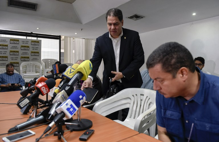 """Opposition lawmaker Luis Florido (C) gets ready to take part in a press conference in Caracas on December 4, 2017.  Opposition representatives in the negotiations with the government of Nicolas Maduro asked for """"patience"""" to seal agreements, although they emphasized """"the urgency"""" to provide solutions for the shortage of foods and medicines in Venezuela. / AFP PHOTO / JUAN BARRETO"""