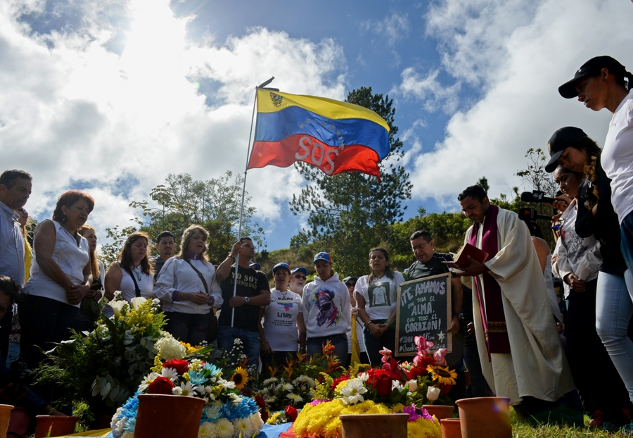 Former elite police officer Oscar Perez's relatives and friends attend a mass next to his gravesite at a cemetery in Caracas on January 21, 2018. Perez's body was burried by the government early in the morning on January 21 against his family will. He was Venezuela's most wanted man since June when he flew a stolen police helicopter over Caracas dropping grenades on the Supreme Court and opening fire on the Interior Ministry, had gone on social media while the operation was under way on January 16 to say he and his group wanted to surrender but were under unrelenting sniper fire. That has raised questions about the government's account that the seven dissidents killed had opened fire on police who had gone to arrest them. / AFP PHOTO / Federico PARRA