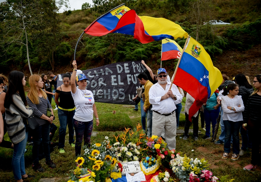 Former elite police officer Oscar Perez's supporters hold a national flag next to his gravesite at a cemetery in Caracas on January 21, 2018. Perez's body was burried by the government early in the morning on January 21 against his family will. He was Venezuela's most wanted man since June when he flew a stolen police helicopter over Caracas dropping grenades on the Supreme Court and opening fire on the Interior Ministry, had gone on social media while the operation was under way on January 16 to say he and his group wanted to surrender but were under unrelenting sniper fire. That has raised questions about the government's account that the seven dissidents killed had opened fire on police who had gone to arrest them. / AFP PHOTO / Federico PARRA