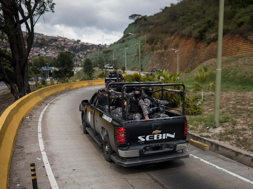 """CAR14. CARACAS (VENEZUELA), 15/01/2018.- Agentes de las Fuerzas Armadas Bolivarianas cruzan en una camioneta hacia el lugar donde se realiza una operación contra el grupo liderado por el policía Óscar Pérez hoy, lunes 15 de enero de 2018, en el barrio El Junquito, en Caracas (Venezuela). Las autoridades venezolanas desarticularon hoy el grupo liderado por el policía Oscar Pérez, acusado de """"ataque terrorista"""" al Supremo, e informaron de haber """"abatido"""" a un grupo no identificado de sus miembros y detenido a cinco. EFE/Miguel Gutiérrez"""