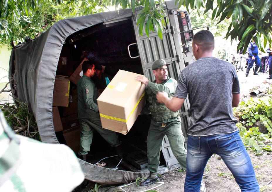 """Funcionarios retirando material de """"elecciones"""" del 20M. Foto: El Siglo"""