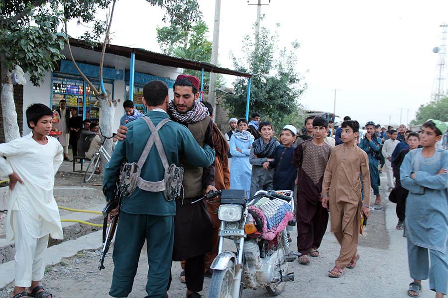 KDZ01. KUNDUZ (AFGANISTÁN), 15/06/2018.- Un supuesto miliciano talibán saluda a un policiía afgano mientras un grupo de talibanes visitan un bazar para mezclarse con la población como gesto de buena voluntad en medio del alto fuego parcial anunciado por los talibanes afganos por la celebración del Eid al Fitr en Kunduz (Afganistán) hoy, 15 de junio de 2018. EFE/ Stringer Entra en vigor el alto el fuego temporal de los talibanes en Afganistán