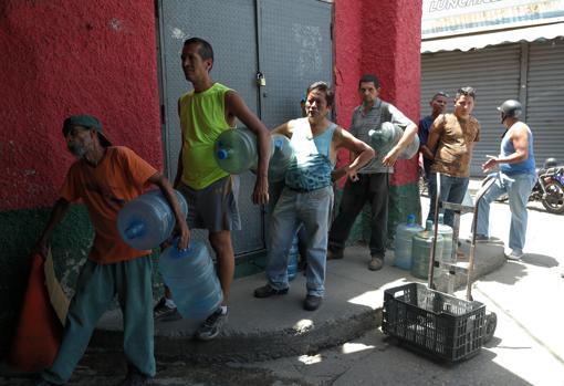 Ciudadanos hacen fila para llenar los bidones en la fábrica de hielo - Mariana Navas, Foto:ABC