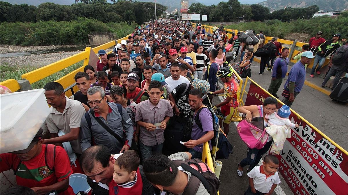 TOPSHOT - Venezuelan citizens cross the Simon Bolivar international bridge from San Antonio del Tachira in Venezuela to Norte de Santander province of Colombia on February 10  2018  Oil-rich and once one of the wealthiest countries in Latin America  Venezuela now faces economic collapse and widespread popular protest     AFP PHOTO   GEORGE CASTELLANOS