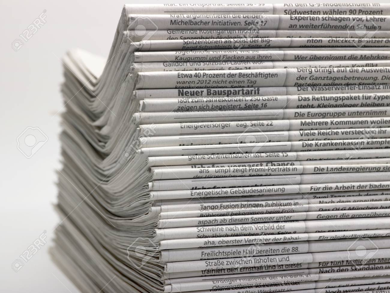 lots of stacked newspapers in light back