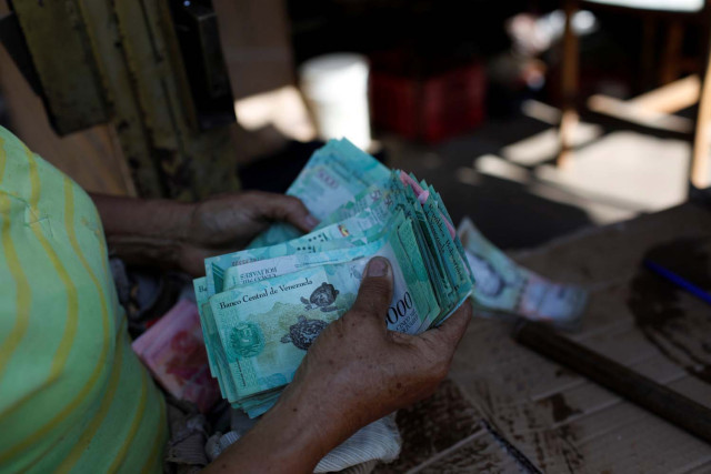 A woman counts Venezuelan bolivar notes in her stall at Las Pulgas market in Maracaibo, Venezuela July 26, 2018. REUTERS/Marco Bello